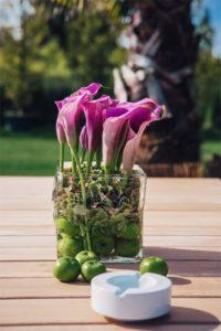 Grün pinke Event Dekoration auf einem Teak Tisch. Er lässt sich bspw. zusammen mit Pflanzen mieten.