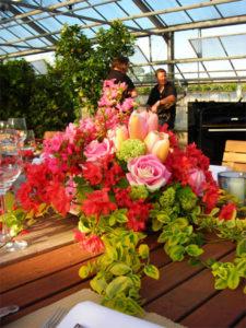 Großer Blumenstrauß auf einer Teaktafel. Umrahmt von Mietpflanzen